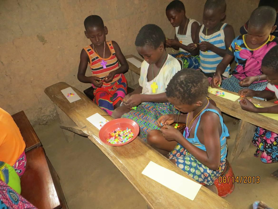 The children working on their bracelets (above) and proudly displaying their colorful beaded bracelets (below)